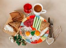 Köstliches Frühstück von den Eiern, Brot mit Butter, Wurst auf der Colorfull-Platte Kaffee, roter Saft mit weißen Blumen Stockfotos