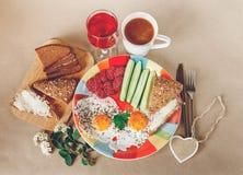 Köstliches Frühstück von den Eiern, Brot mit Butter, Wurst auf der Colorfull-Platte Kaffee, roter Saft mit weißen Blumen braun Stockbilder