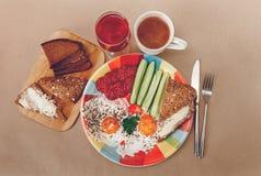 Köstliches Frühstück von den Eiern, Brot mit Butter, Wurst auf der Colorfull-Platte Kaffee, roter Saft mit weißen Blumen Messer u Stockfoto