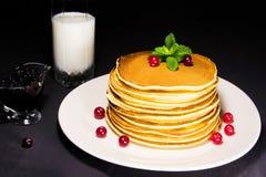Köstliches Frühstück von frischen gebackenen Pfannkuchen mit Milch, Blaubeermarmelade und frischer Moosbeere Stockbild