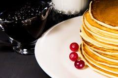 Köstliches Frühstück von frischen gebackenen Pfannkuchen mit Milch, Blaubeermarmelade und frischer Moosbeere Lizenzfreie Stockbilder