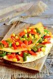 Köstliches Gemüseomelett auf einem hölzernen Brett Gebratenes Omelett angefüllt mit rotem und grünem grünem Pfeffer und Mais Lizenzfreie Stockbilder