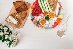 Köstliches geschmackvolles Frühstück von den Eiern, Brot mit Butter, Wurst auf der bunten Platte Wunsch-Herz-Karte Blumen Weißer  Lizenzfreie Stockbilder