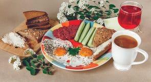 Köstliches geschmackvolles Frühstück von den Eiern, Brot mit Butter, Wurst auf der Colorfull-Platte Kaffee, roter Saft mit weißen Stockbild