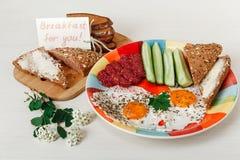 Köstliches geschmackvolles Frühstück von den Eiern, Brot mit Butter, Wurst auf der Colorfull-Platte Kaffee, roter Saft mit weißen Stockfoto