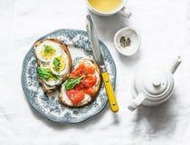 Köstliches gesundes Frühstück oder Imbiss - Käse der Sandwiche mit Sahne, gekochtes Ei und geräucherter Lachs auf einem hellen Hi lizenzfreie stockbilder