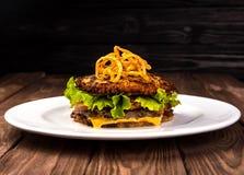 Köstliches Hamburgerkartoffelpfannkuchenbrötchen Latkeburger mit Kopfsalat, Käse, Tomaten auf hölzernem schwarzem Hintergrund und Stockfotografie
