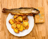 Köstliches knuspriges Brot, geräucherte Fische und Ofenkartoffeln Lizenzfreies Stockfoto