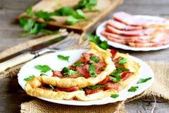 Köstliches Speckomelett Gebratenes Omelett mit Speck und Petersilie für Frühstück Speckscheiben auf einer Platte, Messer, Gabel,  Lizenzfreies Stockfoto
