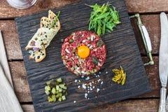Köstliches Tatarbeefsteak mit Eigelb, Kapriolen, Frühlingszwiebel und Brot lizenzfreie stockfotos