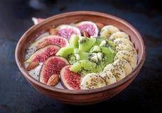 Köstliches und gesundes Hafermehl mit Feigen-, Kiwi-, Bananen-, Mandel- und chiasamen lizenzfreies stockfoto