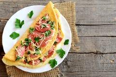 Köstliches Wurst- und Käseomelett auf einer Platte und ein alter hölzerner Hintergrund mit leerem Kopienraum für Text Ärgert Omel Lizenzfreie Stockfotografie