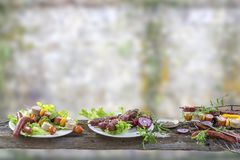 Kött för råkost för grillfest för sortiment för Bbq-partifest olikt, på plattor och raster på en gammal suddig flintaväggbakgrund royaltyfri bild