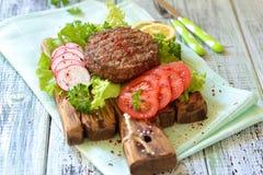 Kött grillade hamburgaren på ett träbräde med grönsaker Arkivbild