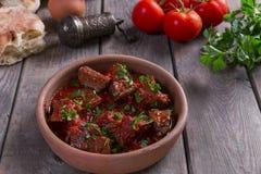 Kött i stek för nötkött för tomatsås i en lerabunke fotografering för bildbyråer