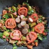 Kött med grönsaker på ett stort uppläggningsfat Arkivfoto