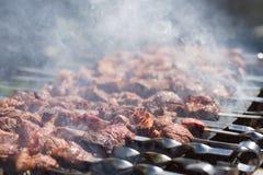 Kött med rök på ett grillfestgaller över kol Grillade kuber av kött på metallsteknålen Kött på steknålar grillas på arkivfoto
