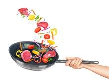 Kött- och blandninggrönsaker faller in i stekpannan Arkivfoto