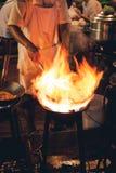 Kött och fisk för matlagning för gatamatkock i en panna med brand och flammor under den Chinatown Bangkok, Thailand royaltyfri fotografi