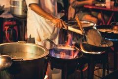 Kött och fisk för matlagning för gatamatkock i en panna med brand och flammor under den Chinatown Bangkok, Thailand arkivfoton