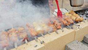 Kött och potatisar på steknålar på grillfesten i röken arkivfilmer