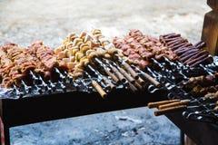 Kött och potatisar som är förberedda för att steka på steknålar Arkivbilder