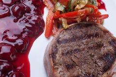 Kött som grillas med sås på vit bakgrund Fotografering för Bildbyråer