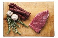 Köttbiff på en skärbräda med korvar Royaltyfri Bild