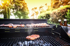 Köttbiffmatlagning på grillfestgallret för utomhus- parti för sommar f royaltyfri fotografi
