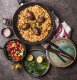 Köttbollar med grönsakris i pannan och sallad som tjänas som på grå färger, stenar köksbordbakgrund med plattor och bestick Royaltyfri Fotografi