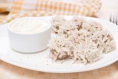 Köttbullar av nötkött med vita ris och yoghurtsås, närbild Arkivfoto