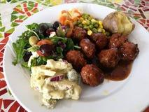 Köttbullar med den nya grönsaken och potatissallad, omslagspotatis, grillade köttbullar i kryddig sötsak och sur tomatsås på vita Royaltyfri Foto