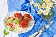 Köttbullar med tomatsås, grönsaker och en sidomaträtt av couscous Royaltyfri Foto