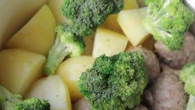 Köttbullar, potatisar och broccoli i matlagningprocessen lager videofilmer