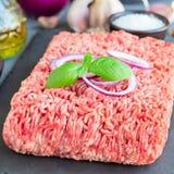 Köttfärs från griskött och nötkött Malt kött med ingredienser för att laga mat på ett mörker kritiserar brädet, fyrkantigt format royaltyfria bilder