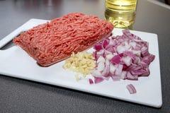 Köttfärs (malt nötkött) med löken, vitlök och olja på skärbräda arkivbilder