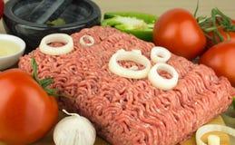 Köttfärs på skärbräda och grönsaker på träbakgrund arkivbild