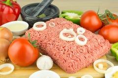 Köttfärs på skärbräda och grönsaker på träbakgrund royaltyfria foton