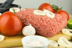 Köttfärs på skärbräda och grönsaker på träbakgrund arkivfoto
