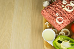 Köttfärs på skärbräda och grönsaker på träbakgrund royaltyfri foto