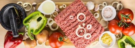Köttfärs på skärbräda, på ett pund och grönsaker på träb fotografering för bildbyråer