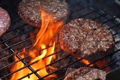 Kötthamburgare för hamburgaren som grillas på flamman, grillar Royaltyfri Bild