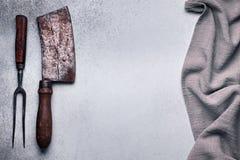 Köttköttyxa och gaffel på konkret bakgrund fotografering för bildbyråer