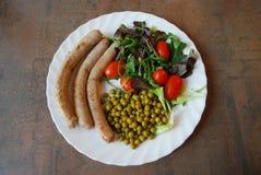Köttkorvar, gröna ärtor och grönsallat Arkivfoton