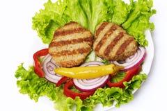 Köttkotlett med grönsaksallad arkivbild