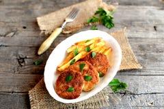 Köttkotletter och stekte potatisar på en platta, en gaffel, en kvist av persilja och säckväv på gammal wood bakgrund royaltyfria foton