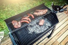 Köttmatlagning på grillfestgallret för utomhus- parti för sommar arkivbilder
