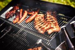 Köttmatlagning på grillfestgallret för utomhus- parti för sommar arkivfoto