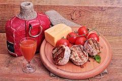 köttmedaljonger med körsbärsröda tomater Arkivfoto