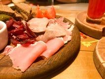 Köttmellanmål med alkohol från kött, skinka, basturma med sås på träställningar på tabellen i ett kafé, stång, restaurang arkivfoton